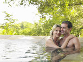 Couple embracing in pool smiling — Stock fotografie