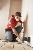 Man wearing face mask sanding wall — Stock Photo