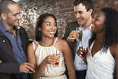 Two couples holding drinks standing in bar — Stock Photo