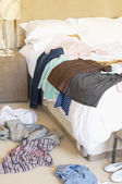 Clothes on Floor and Bed — Stock Photo