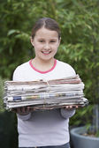 Girl holding bundle of  paper — Stock Photo