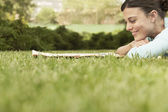 Woman lying on grass reading newspaper — Stock Photo