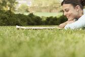 Woman lying on grass reading newspaper — Stock Photo