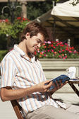 Man at Cafe reading guidebook — Stock Photo