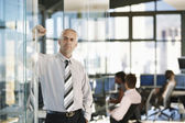 Businessman leaning on door in office — Stock Photo