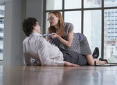 Woman seducing man in office — Stock Photo