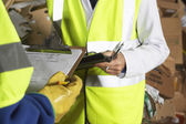 Factory workers holding clipboards — Stock Photo