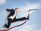 Business man jumping through red tape — Stock Photo