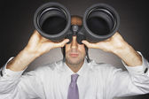 Balding businessman looking through binoculars — Stock Photo