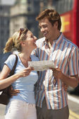 Couple on London street reading map — Stock Photo