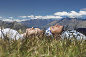 Man and woman lying in field — Stockfoto