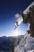 Snowboarder jumping from mountain ledge — Stock Photo