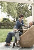 Woman sitting on husband's laps — Stock Photo