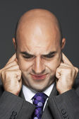 Bald businessman with fingers in ears — Stock Photo