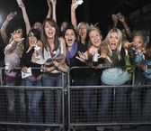 Fans leaning over barrier and screaming — Stock Photo