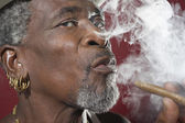 African Man exhaling cigar smoke — Stock Photo