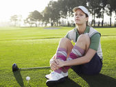 Golfer sitting on court — Stock Photo