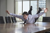 Businessman sliding on stomach on table — Stock Photo