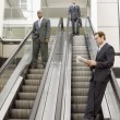 Businessmen on escalators — Stock Photo #33840333