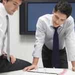 Businessmen looking in file folder — Stock Photo #33843359