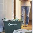 Recycling container and waste papers with person — Stock Photo #33840391