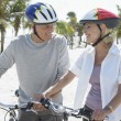 Couple with bicycles on tropical beach — Stock Photo