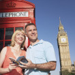 Couple with guidebook by London phone booth — Stock Photo #33841399