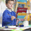 Stock Photo: Boy painting in art class