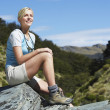 Stock Photo: Womsitting on boulder