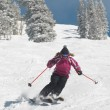 Stock Photo: Young womskiing down