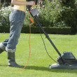 Foto Stock: WomMowing Lawn