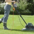 Stock Photo: WomMowing Lawn