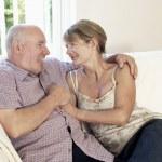 Middle Aged Couple sitting on sofa — Stock Photo