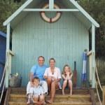 Family sitting in beach hut — Stock Photo