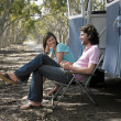 Couple sitting in deck chairs beside camper van — Stock Photo #33845421