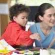 Art teacher and boy painting — Stock Photo