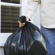 Man putting garbage bag into trash can — Stock Photo