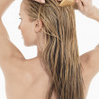 Young Blond Woman Combing Hair — Stock Photo #33846647
