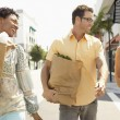 Stock Photo: Friends walking with groceries