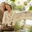 Tourist Couple sitting on wall — Stock Photo