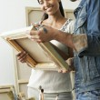 Stock Photo: Couple looking at canvases in artist studio