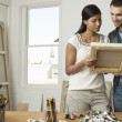 Multiethnic couple looking at canvases — Stock Photo #33849137