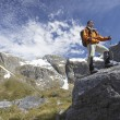 Stock Photo: Hiker on top of boulder