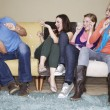 Women throwing popcorn at friend on sofa — Stock Photo