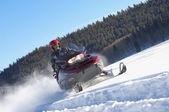 Man snowmobiling through snow — Stock Photo