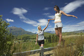 Woman helping another woman walk along fence — Stock Photo
