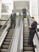 Businessmen on escalators — Stock Photo