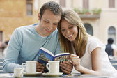Couple looking at guidebook — Stock Photo