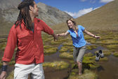 Man helping woman wade through pond — Stock Photo