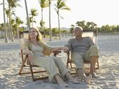 Senior couple relaxing on deckchairs — Stock Photo